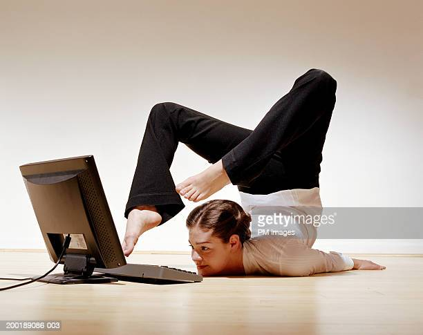 Businesswoman using laptop with toes
