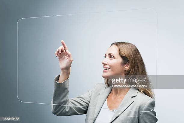 Businesswoman using large transparent touch screen