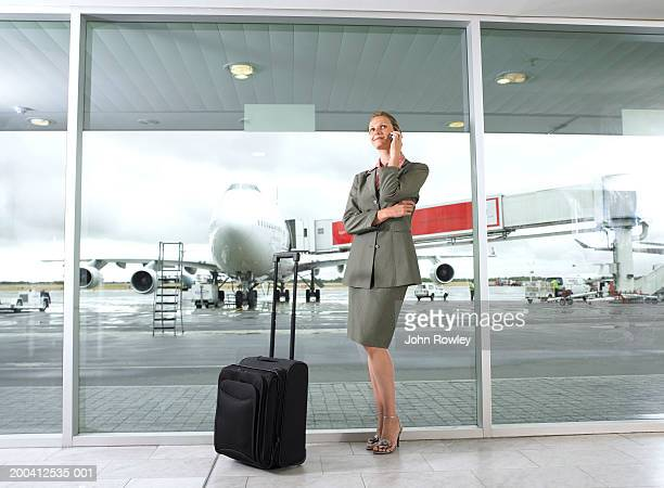Businesswoman using mobile in airport, standing by luggage, smiling