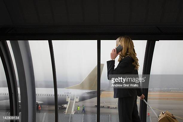 businesswoman using mobile in an airport terminal