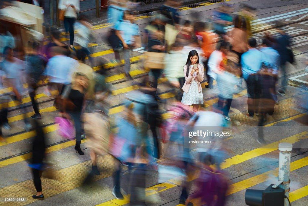 Imprenditrice che usa il telefono cellulare tra la folla : Foto stock