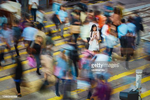 businesswoman using mobile phone amidst crowd - wireless technology foto e immagini stock