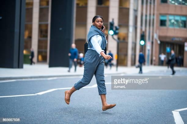 Mulher de negócios usando o telefone móvel e cruzamento da rua em Londres