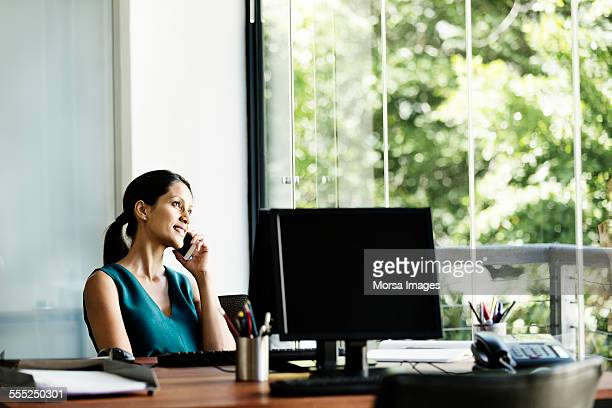 Businesswoman using mobile phone at computer desk
