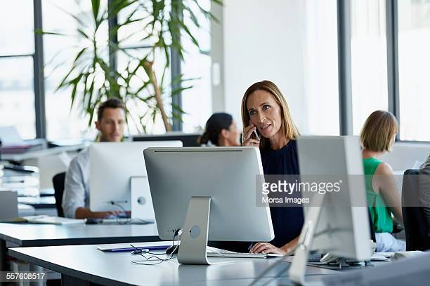 Businesswoman using mobile phone at desk in office