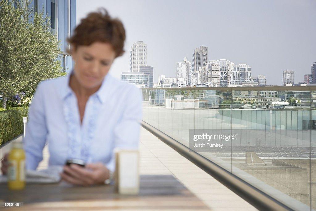 Businesswoman using mobile phone, defocussed  : Stock-Foto