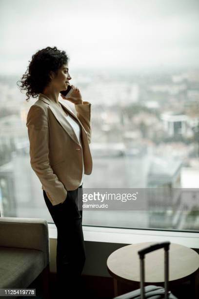 femme d'affaires à l'aide de téléphone mobile dans une chambre d'hôtel - directrice photos et images de collection