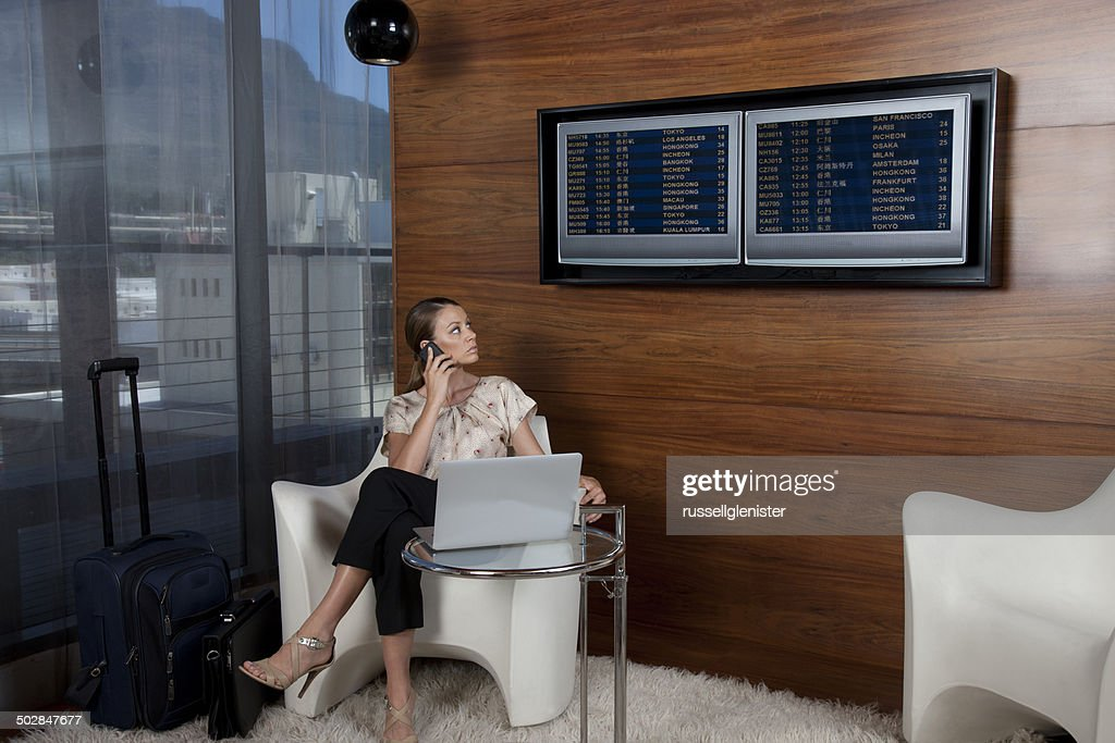 Businesswoman using mobile phone in airport lounge : Stock Photo
