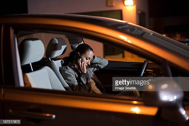 Businesswoman using mobile phone in car at night