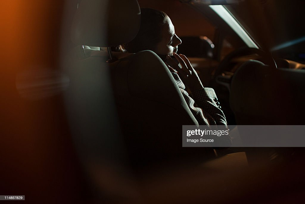 Businesswoman using mobile phone in car at night : Stock Photo