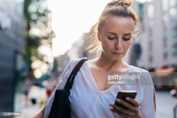 Businesswoman using mobile phone in city.