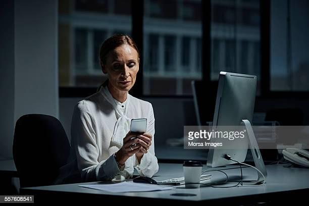 Businesswoman using mobile phone in dark office