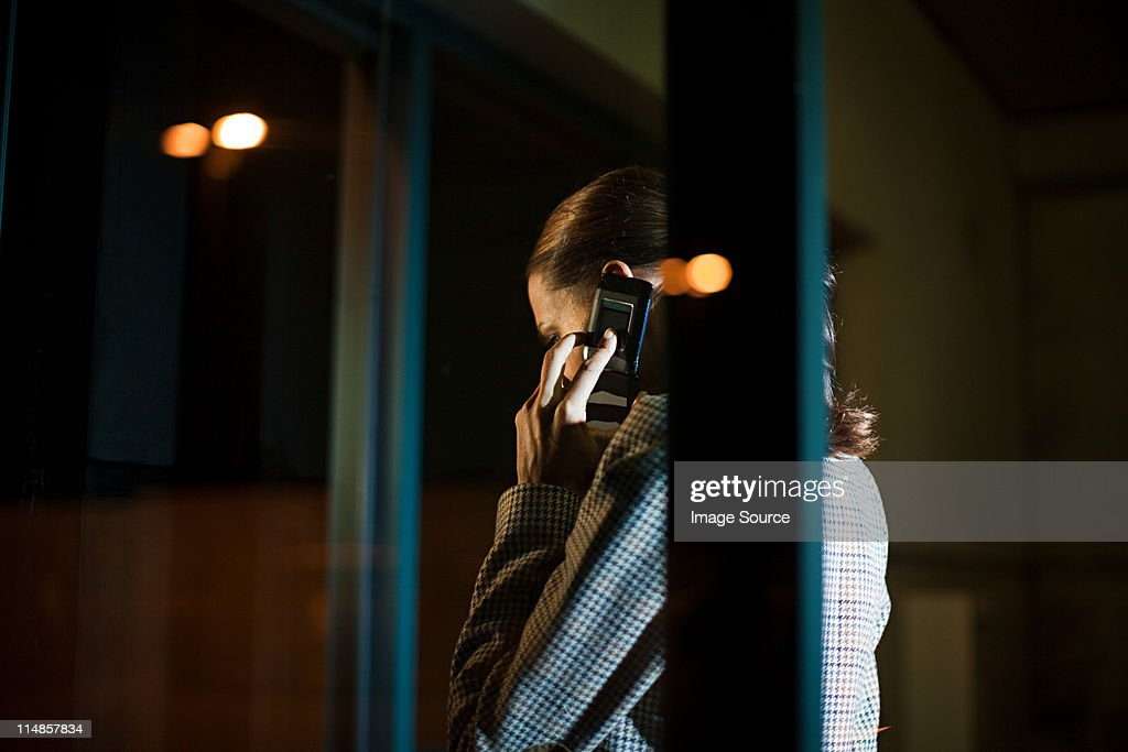 Businesswoman using mobile phone in office at night : Stock Photo
