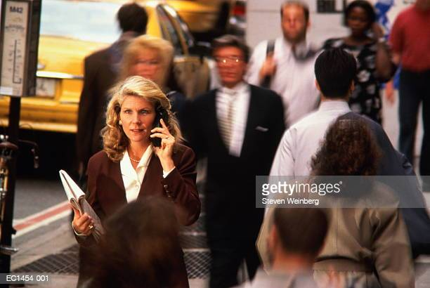 Businesswoman using mobile phone, New York City, USA (blurred motion)