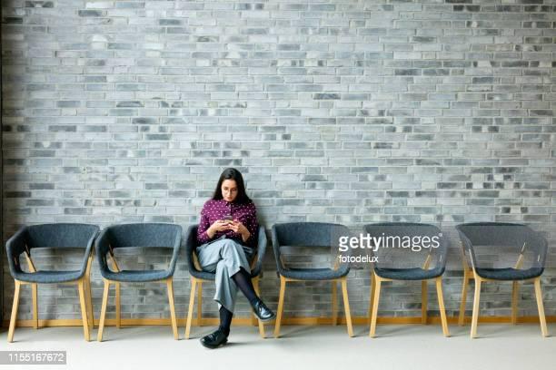 geschäftsfrau mit handy - wartezimmer stock-fotos und bilder