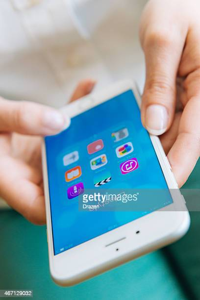 Businesswoman using new Apple iPhone 6 and lifestyle apps
