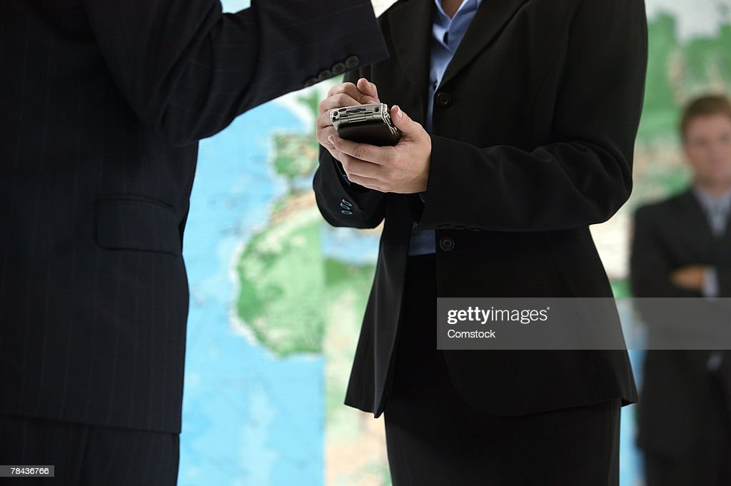 Businesswoman using PDA with world map behind her : Stockfoto
