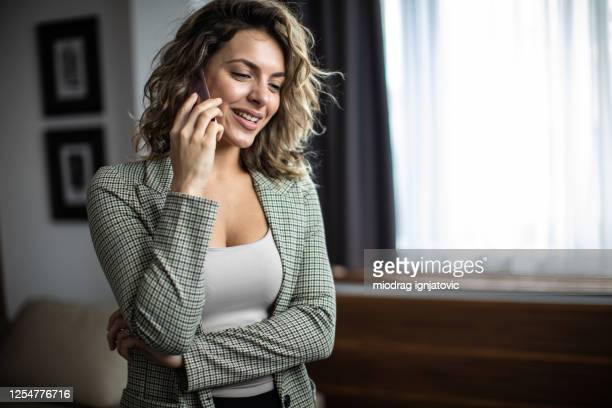 businesswoman using phone at hotel room - guest stock pictures, royalty-free photos & images