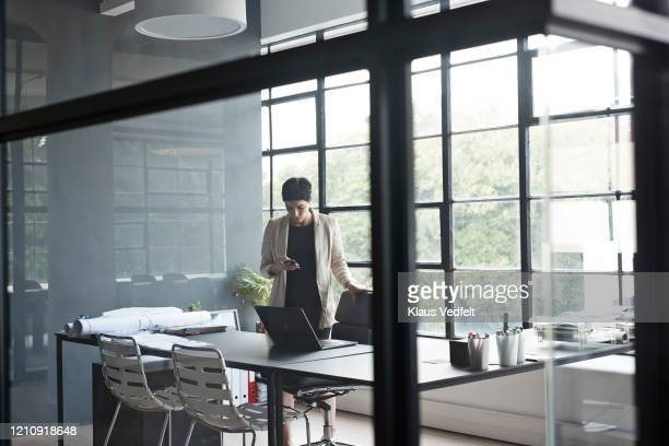 businesswoman using phone at office desk - cream coloured blazer stock pictures, royalty-free photos & images