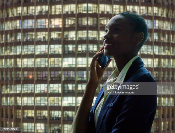businesswoman using phone, facade of neighbouring building in background - nairobi stock pictures, royalty-free photos & images