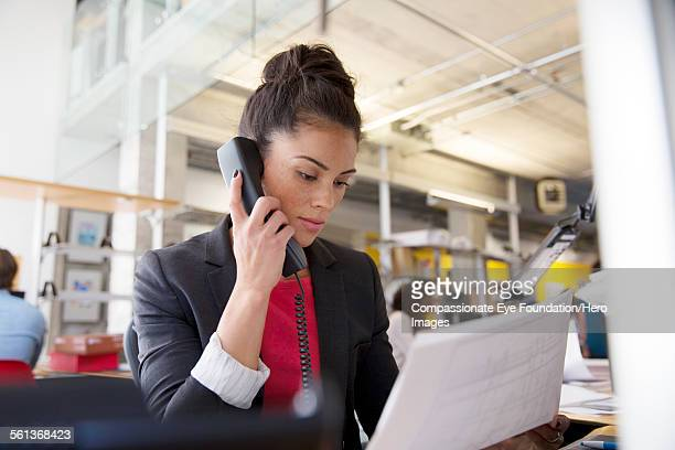 Businesswoman using phone in modern office