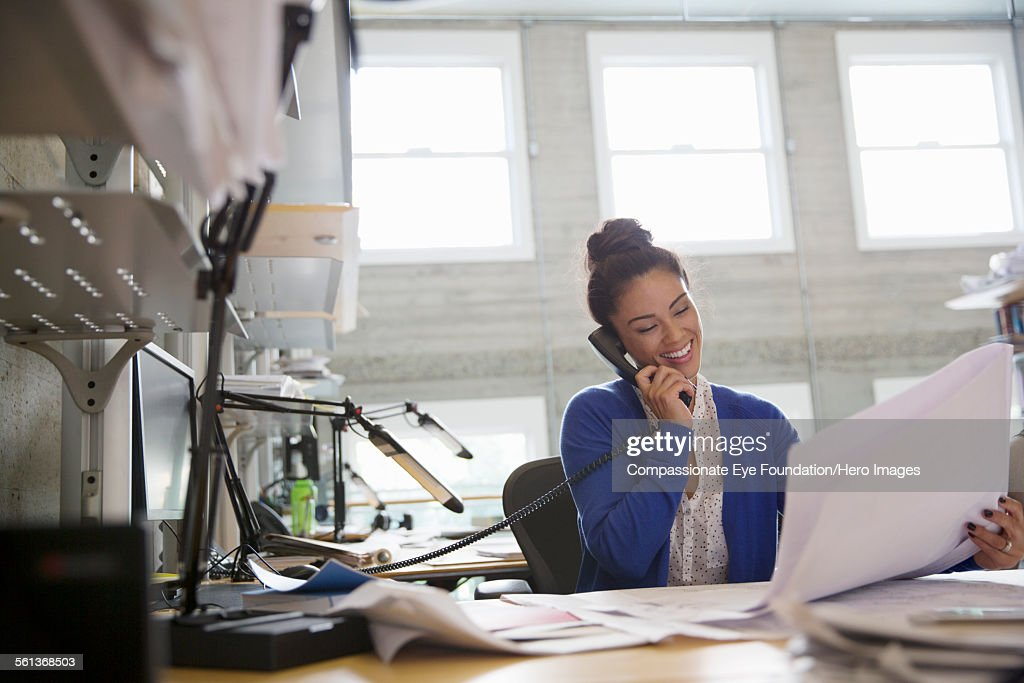 Businesswoman using phone in modern office : Stock Photo