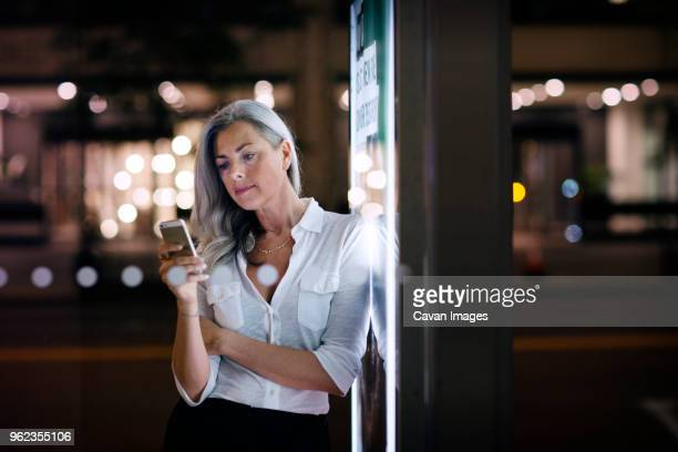 Businesswoman using phone while leaning on bus stop poster in city