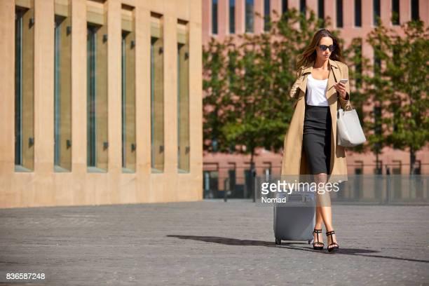 荷物を引きながら携帯電話を使用して実業家