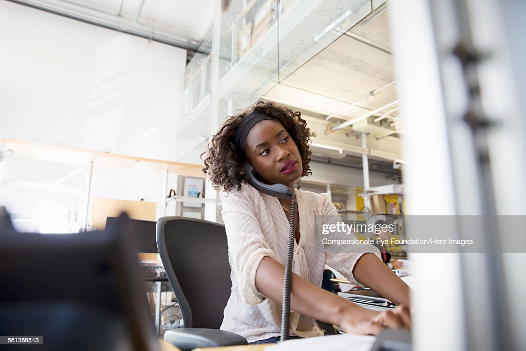 Businesswoman using phone while working in office : Stock Photo