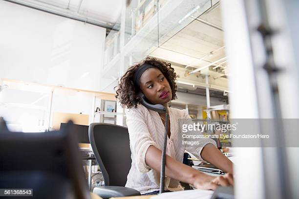 Businesswoman using phone while working in office
