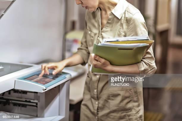 Businesswoman using photocopier in office