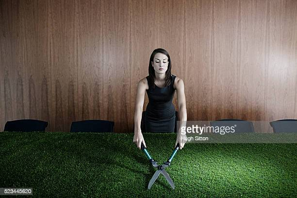 businesswoman using shears to cut grass on boardroom table - hugh sitton stockfoto's en -beelden