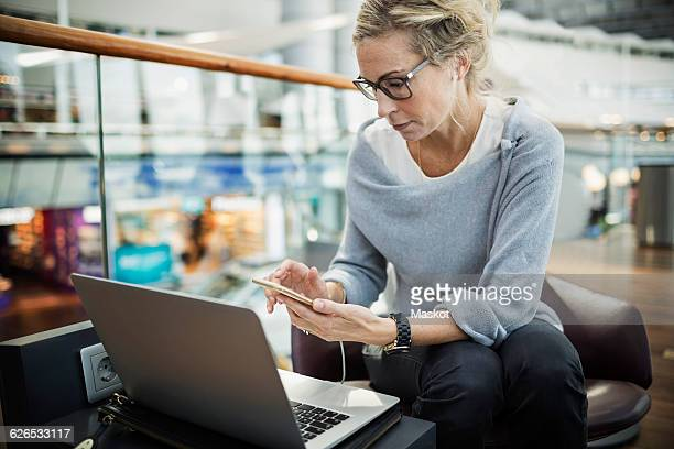 businesswoman using smart phone and laptop at airport lobby - one mature woman only stock pictures, royalty-free photos & images