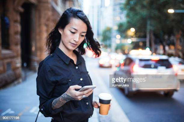 Businesswoman using smart phone and waiting for a taxi