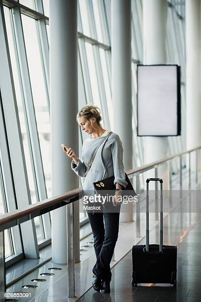 Businesswoman using smart phone at airport