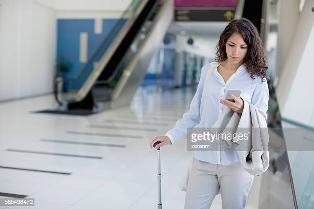 Businesswoman using smart phone at airport terminal