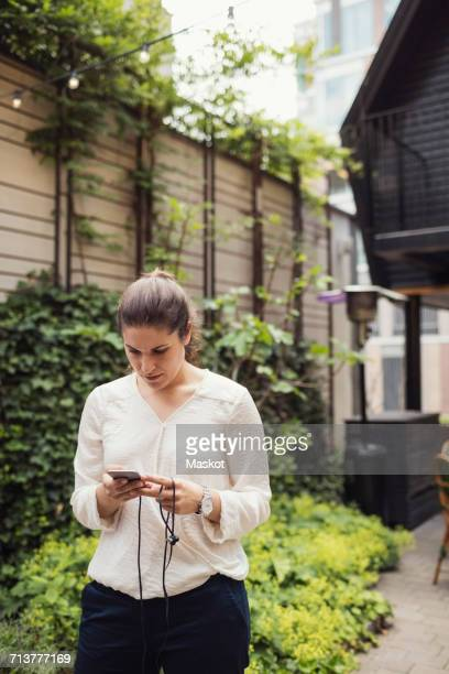 Businesswoman using smart phone at office yard