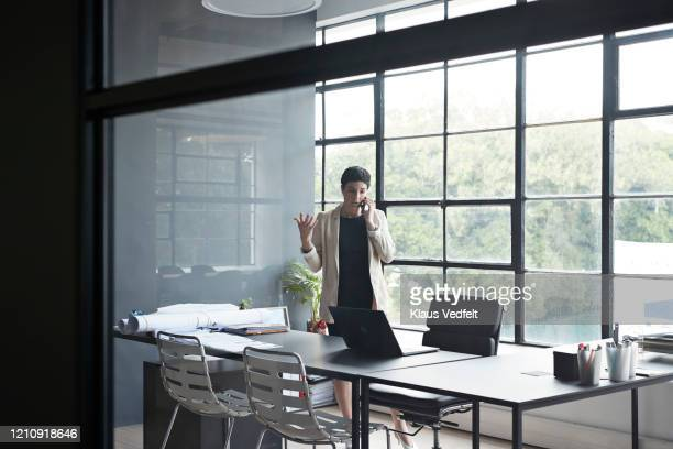 businesswoman using smart phone at workplace - cream coloured blazer stock pictures, royalty-free photos & images