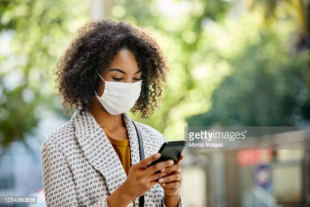 businesswoman using smart phone during covid-19 pandemic in city, she is wearing protective face mask - aplanar a curva imagens e fotografias de stock