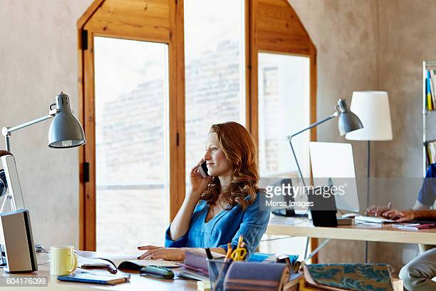 businesswoman using smart phone in creative office - one young woman only stock pictures, royalty-free photos & images
