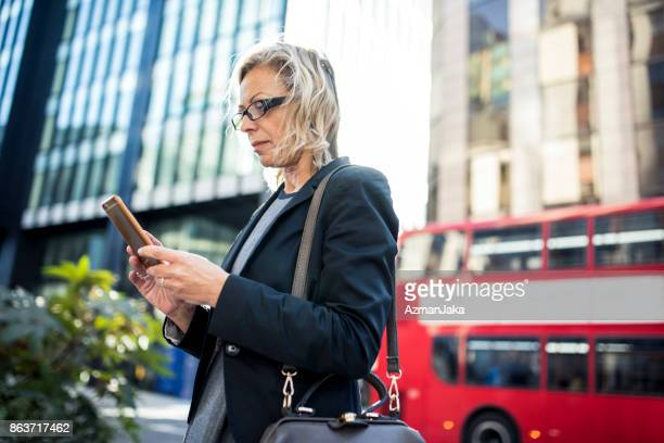 Businesswoman using smart phone in London