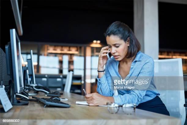 Geschäftsfrau mit Smartphone in Textilfabrik