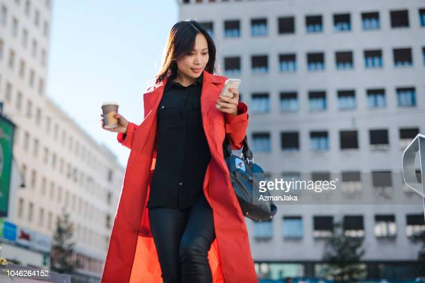 businesswoman using smart phone in the city - vietnamese ethnicity stock pictures, royalty-free photos & images