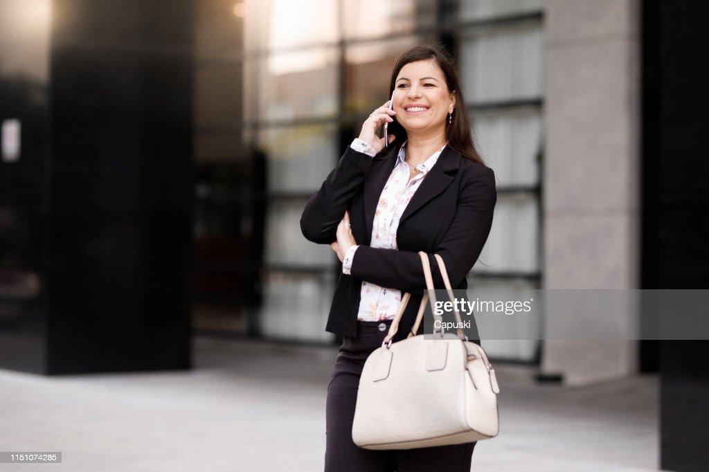 Mulher de negócios que usa o telefone esperto : Foto de stock