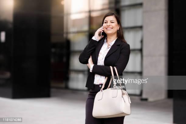 mulher de negócios que usa o telefone esperto - bolsa objeto manufaturado - fotografias e filmes do acervo