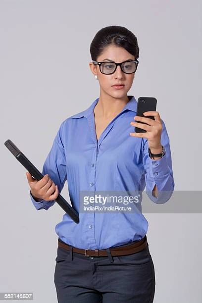 Businesswoman using smart phone while holding laptop against gray background