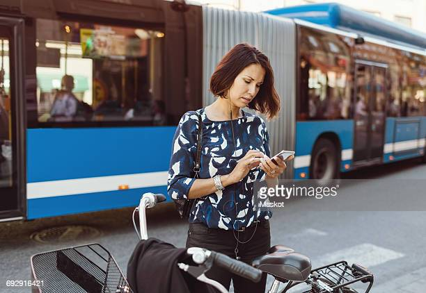 Businesswoman using smart phone while standing with bicycle on city street