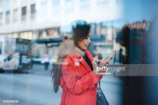 businesswoman using smart phone while waiting for a bus - red stock pictures, royalty-free photos & images