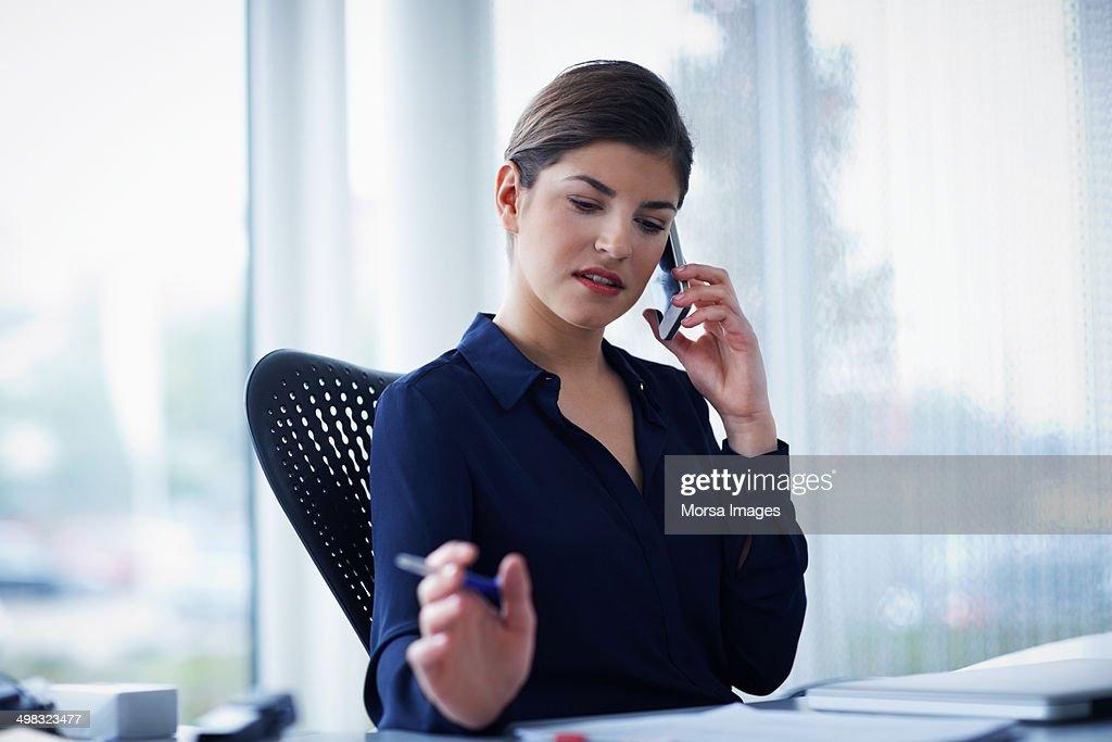 Businesswoman using smart phone while working : Stock Photo