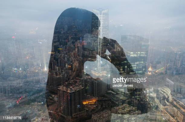 businesswoman using smartphone and hong kong cityscape, composite image - erin james stock-fotos und bilder